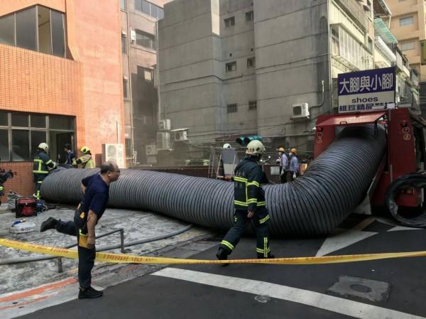 台北市松江路125號發生火警,消防人員進行排煙。(記者劉慶侯翻攝)
