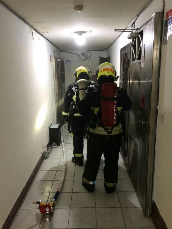 消防人員拉起水線急衝四樓。(記者許國楨翻攝)