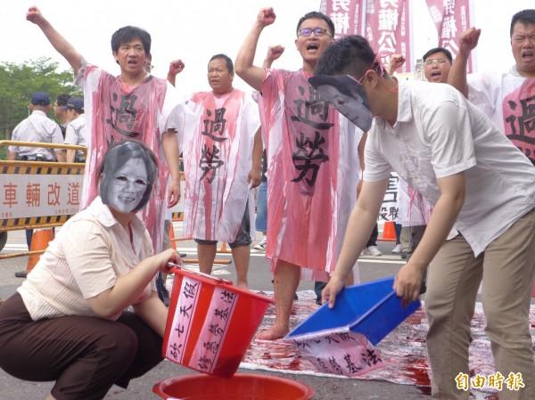勞權公投聯盟上演行動劇,演員戴上總統蔡英文、行政院長賴清德面具,向勞工身上澆下血色液體。(記者李雅雯攝)