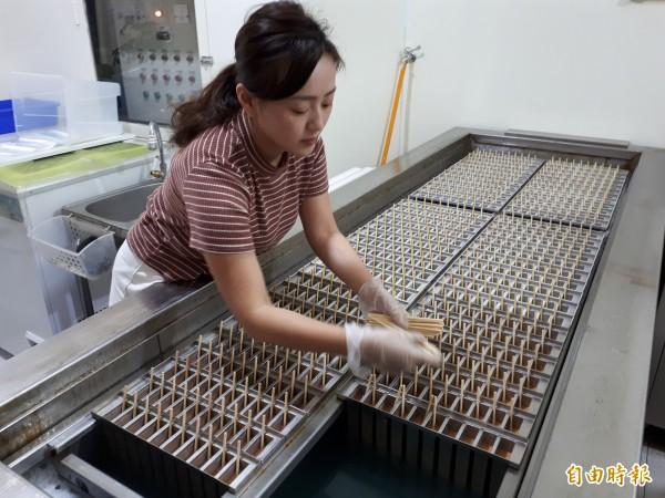 新竹市「814大同冰店」採傳統製冰方式,冰棒都是裸冰棒出售,沒有過多包裝,且使用竹子撐著冰棒,所有製冰棒過程都公開透明,一次最多可製600支冰棒,且透過脫冰機,須在1分鐘內裝袋完成。(記者洪美秀攝)