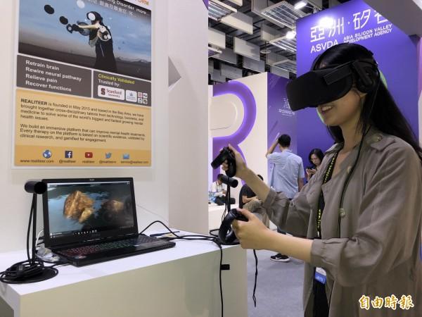 矽谷新創團隊Realiteer,現身台北國際電腦展Innovex館,展示用VR進行物理治療的神奇效果,圖中為團隊成員林佑柔親自展示打怪也能減緩神經痛。(記者陳炳宏攝)
