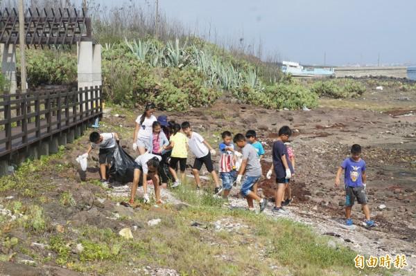 五德國小配合世界海洋日活動,一至五年級在碼頭淨灘。(記者劉禹慶攝)
