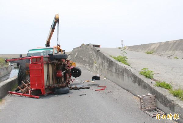 蚵車疑似爬坡時動力不足,從旁斜坡翻落路面。(記者陳冠備攝)