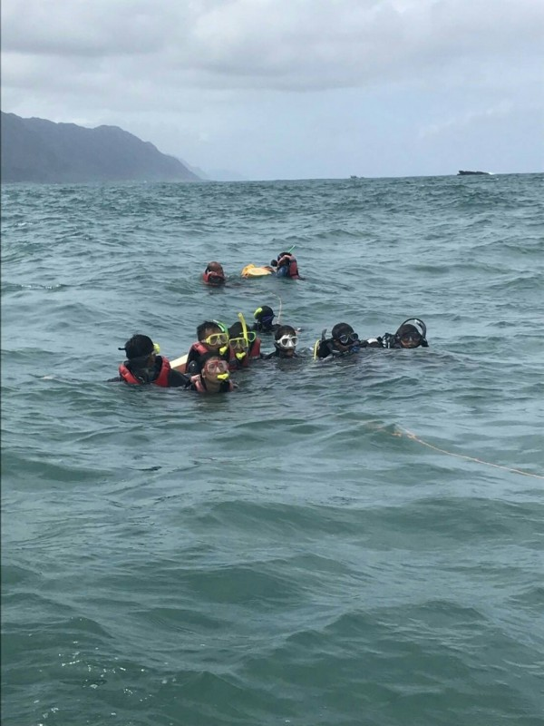海巡署東部分署一二岸巡隊石梯守望哨及時發現潛水遊客呼救,出動救生艇將繩索及魚雷浮標投擲給求救遊客,順利將人拖回港內上岸。(海巡署提供)