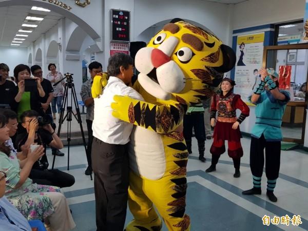 紙風車劇團將於6月23日下午6點在基隆港西三碼頭倉庫演出,圖為基隆市副市長林永發盛讚演出精彩,與老虎戲偶擁抱。(記者俞肇福攝)