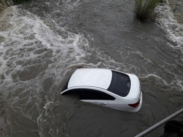 自小客車掉落大湖口溪床,在湍急溪流中觸目驚心。(民眾提供)