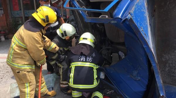 小貨車自撞翻覆,消防隊員搶救受困駕駛。(記者蔡宗勳翻攝)