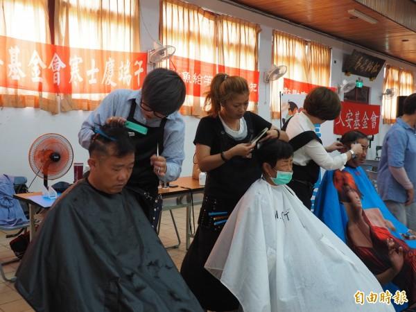 3位美髮師在會場為民眾義剪。(記者王秀亭攝)