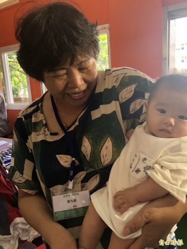 57歲的林姓婦人今開心帶著4個月大的曾孫女珮珮(化名)來參與活動,她說,感謝優衣庫帶來許多的嬰幼兒衣物,讓她一次補足珮珮這一兩年的衣物,縮減經濟壓力。(記者王駿杰攝)