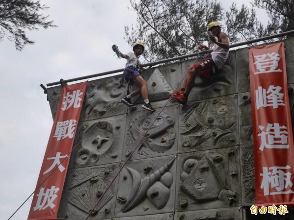 大坡國中畢業生代表攀岩取得畢業證書。(記者許倬勛攝)