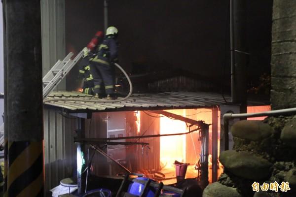 消防隊員冒險爬上屋頂灌救。(記者鄭名翔攝)