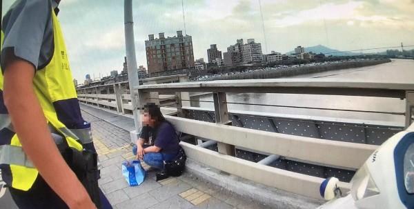 警消趕扺發現,38歲何女坐在橋上人行道。(警方提供)