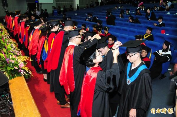 師長為全體畢業生一一正冠與撥穗,祝福畢業生學有所成,展翅高飛。(記者張軒哲攝)