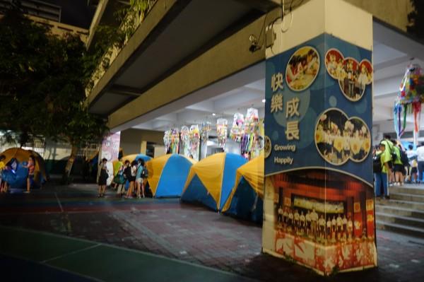 彰化市民生國小百年來第一次,畢業生宿營在校園,為了怕下雨,帳篷紛紛移到走廊下。(記者劉曉欣攝)