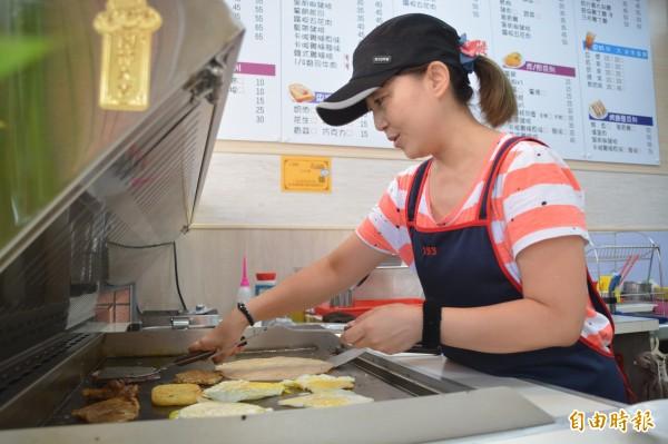 長年站在高溫悶熱煎台前、資歷逾20年的鄭怡華,堅持經營「傳統早餐店」。(記者王峻祺攝)