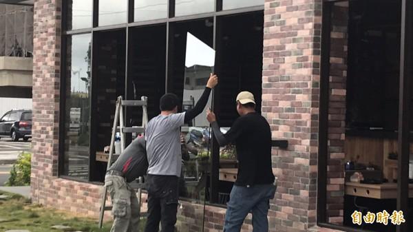 為了防範颱風「瑪莉亞」造成更大的損失,被砸的火鍋店業者今天緊急僱工修復被毀的門窗。(記者黃美珠攝)
