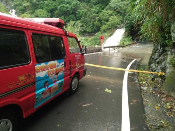 新竹縣122號縣道43K路段嚴重積水,已拉起封鎖線管制人車通行。(圖由新竹縣政府災害應變中心提供)