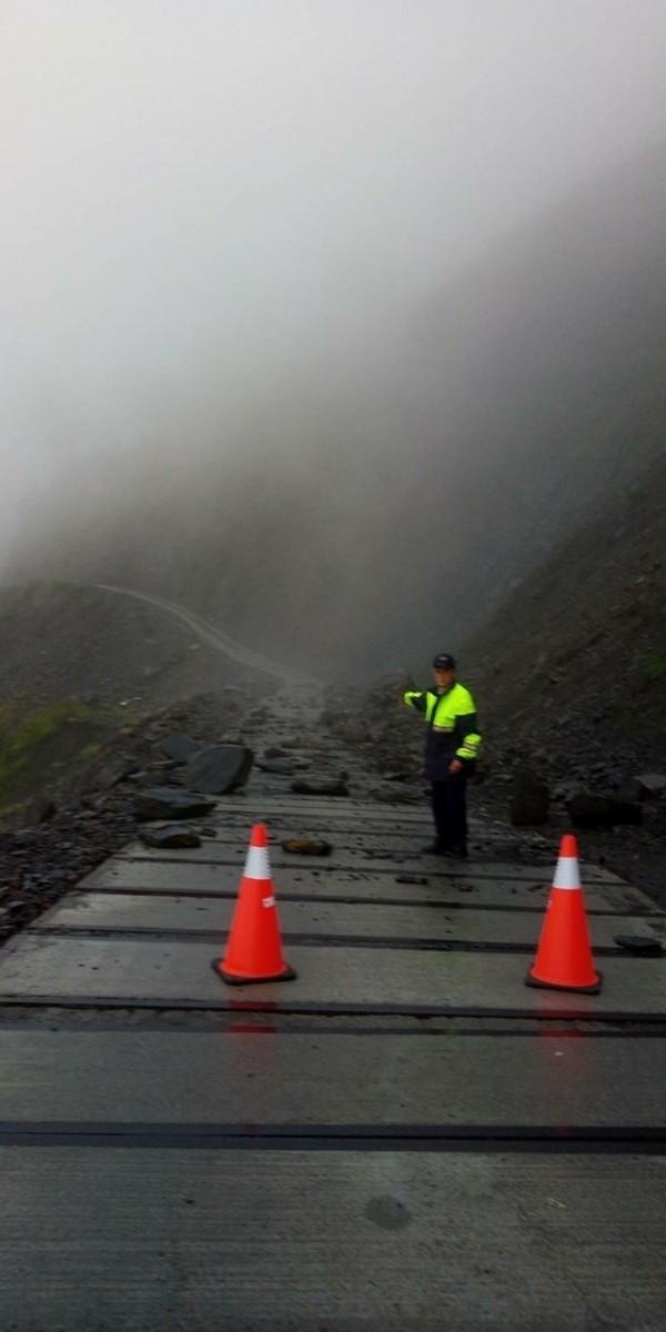 仁愛分局員警在坍方路段擺設警示三角錐,禁止人車通行。(圖:仁愛分局提供)