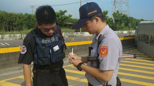 警方對保全人員詢問運鈔車翻覆過程。(記者蘇福男翻攝)