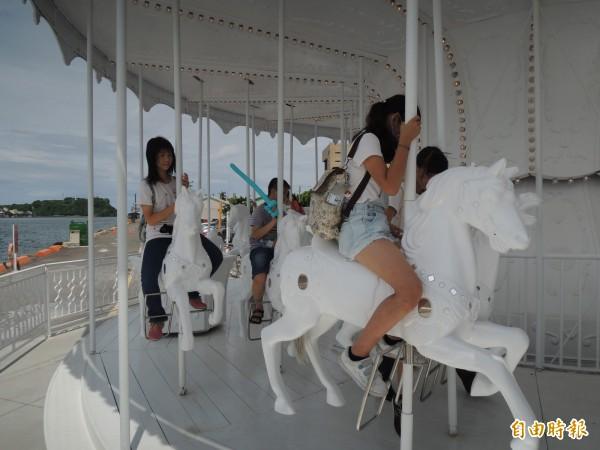 學童率先體驗白色旋轉木馬。(記者王榮祥攝)