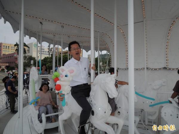 高雄港區土地開發公司董事長郭添貴變孩子王,陪學童一起夢幻一下,他笑說上次搭旋轉木馬是20年前。(記者王榮祥攝)