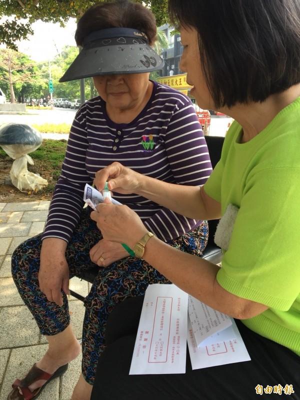 志工邀約民眾進行癌篩。(記者王駿杰攝)