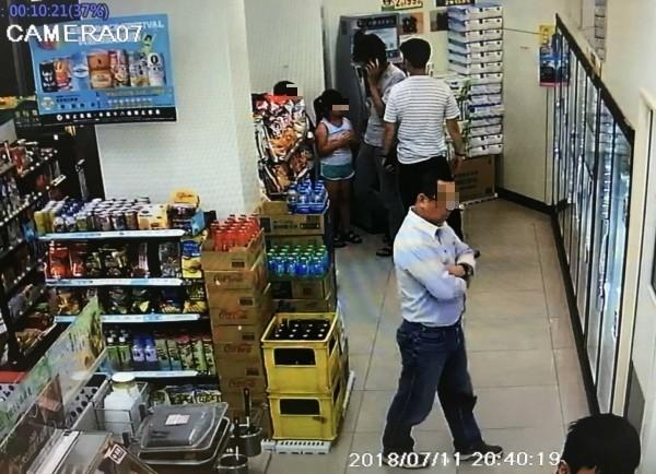 41歲鍾姓男子(ATM前灰色衣)昨晚帶2個小孩到超商ATM提款,與後方羅姓男子(白色橫條)起口角,並當場大打出手,沒想到鍾男2個小時後竟在友人家猝死。(記者廖雪茹翻攝)