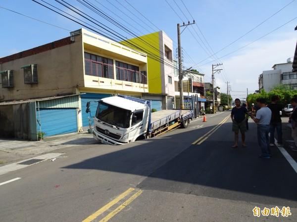 大貨車被馬路吃掉了? 疑是管線漏水掏空肇禍。(記者洪美秀攝)