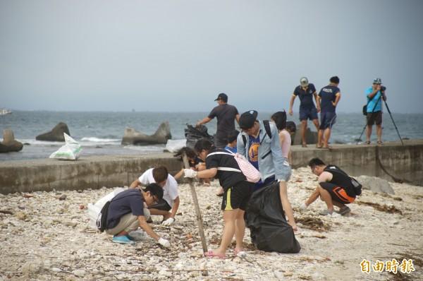大批淨灘客忙著撿拾小琉球白沙灘上的垃圾。(記者陳彥廷攝)
