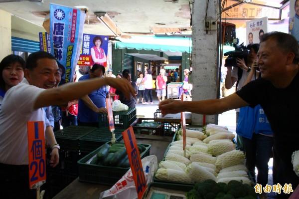 侯友宜在市场扫街拜票外,也和买菜的民众握手互动。(记者邱书昱摄)