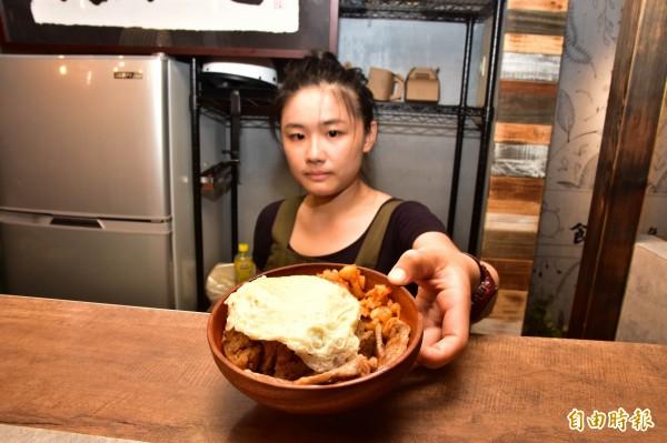黯然銷魂捲,內用以木碗盛裝,古早味油飯蓋上荷包蛋、泡菜、豬排等料,就足以讓夜貓族飽餐一頓。(記者張議晨攝)