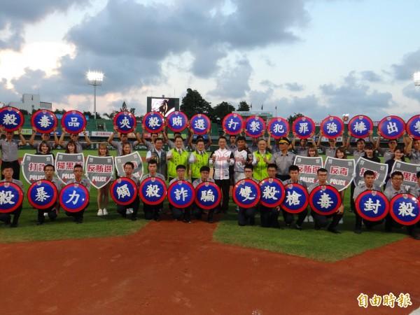 内政部长徐国勇(中著棒球装者)到台南参加结合职棒赛的大型犯罪预防宣导活动。(记者王俊忠摄)