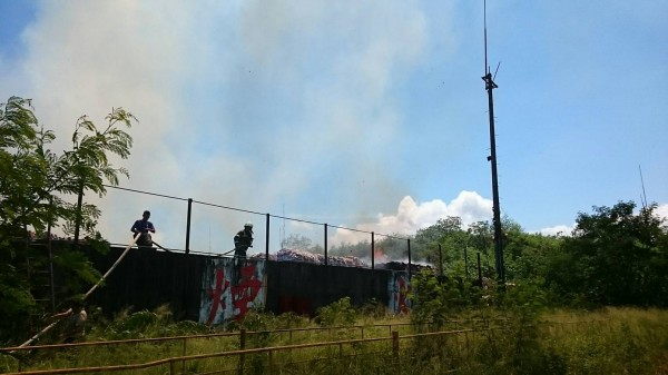 消防人員爬上圍牆搶滅火勢。(記者陳賢義翻攝)