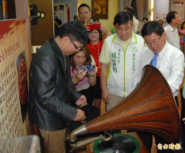 老唱片收藏家黃士豪(左)為彰化市長邱建富(右)示範播放老唱片。(記者湯世名攝)