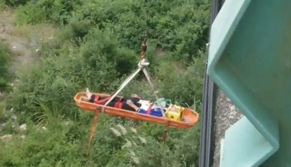 王姓男子墜落溪床礫石區,雙腿嚴重骨折動彈不得,由消防隊吊掛上橋送醫救治。(記者佟振國翻攝)