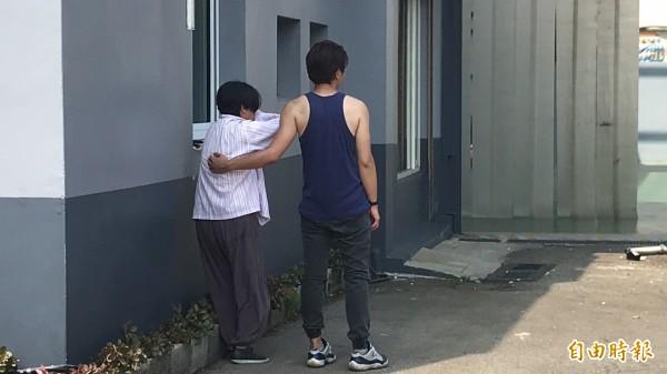 李婦(左)看著自己農地上的鐵皮倉庫被強制執行拆除,難過得掩面痛哭失聲,腳下一個踉蹌差點站不穩,需要旁人扶持。(記者黃美珠攝)