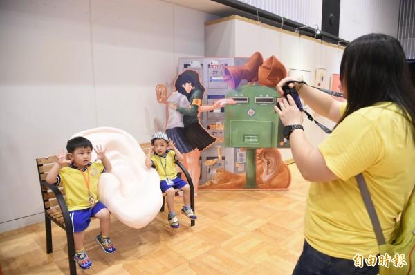 老師帶小朋友來參觀也幫小朋友拍照。(記者張忠義攝)