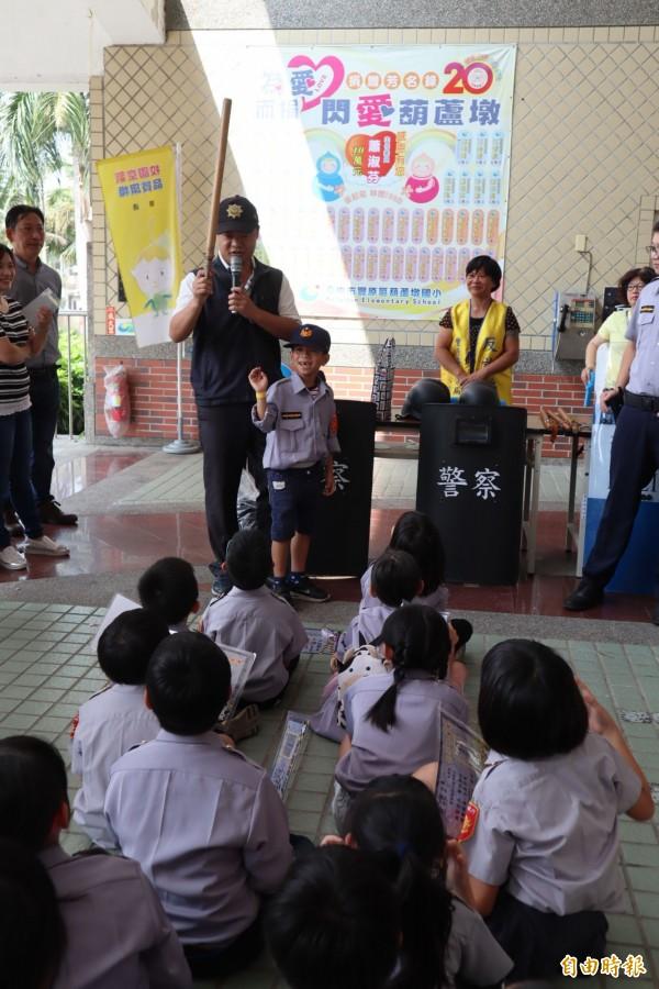 「小小超級戰警」體驗營在葫蘆墩國小舉行,員警教導小朋友警棍的用途。(記者歐素美攝)