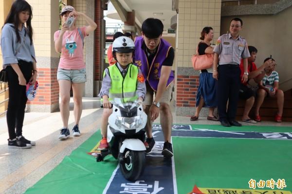 「小小超級戰警」體驗營,小朋友在警察及志工指導下學習騎小小電動警車並學習交通規則。(記者歐素美攝)
