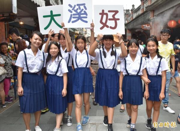 大溪國小學生組成學妹團,穿上舊式制服模擬學姊鳳飛飛當年在草店尾練唱的模樣。(記者李容萍攝)