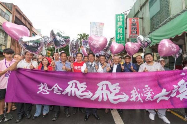 「想念飛飛系列踩街活動」中,鄭文燦(前中)等人帶隊模仿鳳飛飛的團體沿街進行表演。(桃園市政府提供)