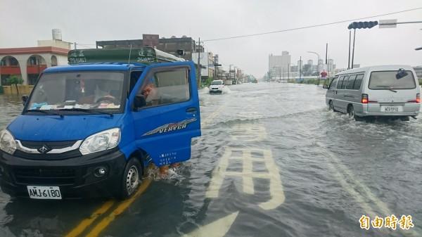 台南市道172線新營往鹽水因水淹到膝蓋,交通受阻中斷,部分車輛冒險涉水通過。(記者楊金城攝)