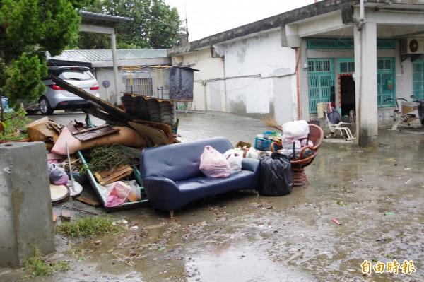 災民將泡水家具堆在門外。(記者曾迺強攝)