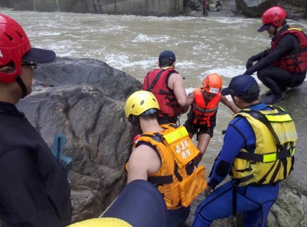 嘉義縣消防局人員在急流中將法國人士與狗救援到安全處所。(記者林宜樟翻攝)