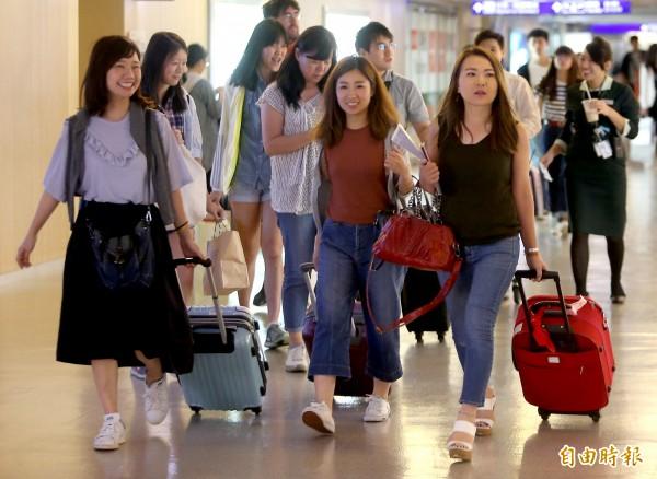 關西機場國際線開放起降後,第一架飛抵台灣的樂桃航空MM-27班機8日傍晚抵達桃園機場,旅客下飛機後面露開心笑容。(記者朱沛雄攝)