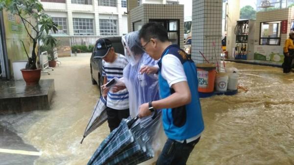 一場大雨,讓國民黨基隆市長參選人謝立功(右)、議長宋瑋莉(中)合體,一同前往西定路會勘淹水災情;謝立功還伸手攙扶宋瑋莉通過積水區。(記者俞肇福翻攝)