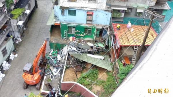 基隆市新西街民宅違建外擴部分,基隆市府今天繼續拆除工作。(記者俞肇福攝)
