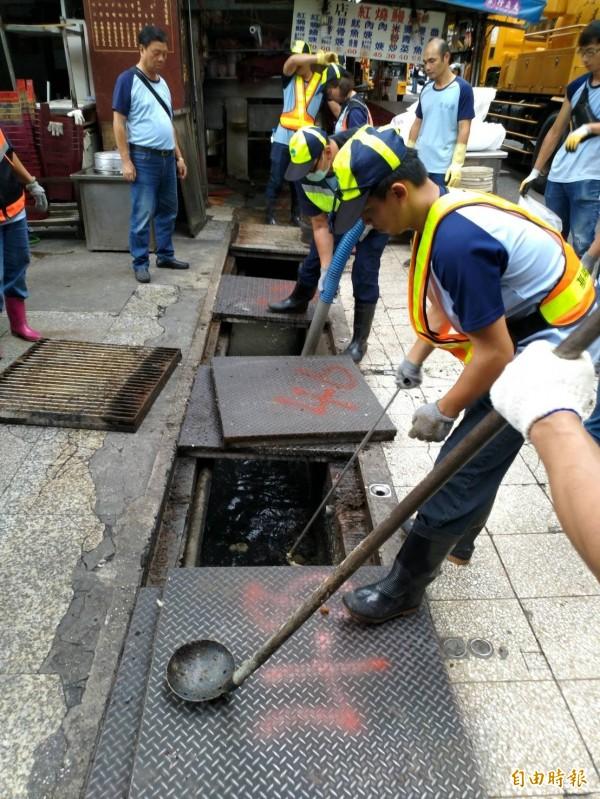 基隆市環保局清潔人員認真疏濬下水道,將累積多時的油汙清理,讓水溝保持暢通。(記者俞肇福攝)
