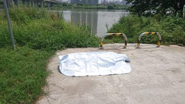 警消人員將該具男浮屍打撈上岸。(記者曾健銘翻攝)