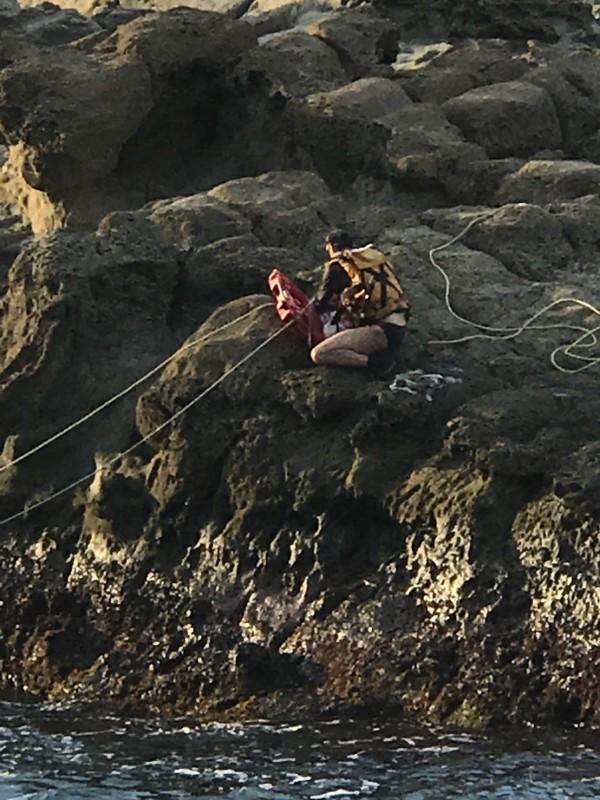 消防人員冒生命危險跳下海游到對岸,再攀爬岩壁,剪繩索、鋸鋼釘。(記者林欣漢翻攝)
